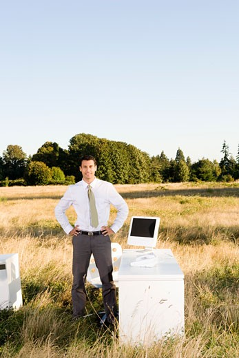 Businessman at desk in field : Stock Photo