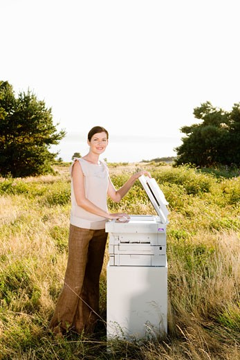 Stock Photo: 1779R-23298 Businesswoman next to copier in field