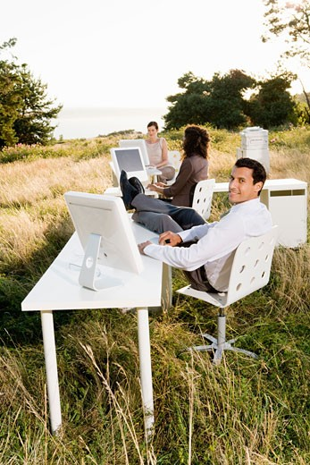 Stock Photo: 1779R-23300 Businesspeople at desks in field