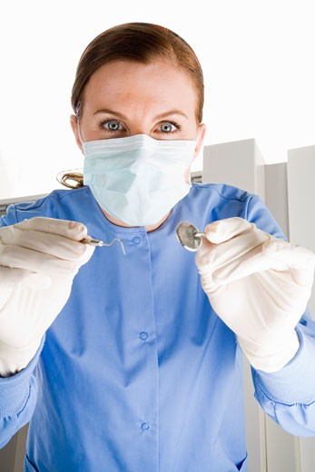 Stock Photo: 1779R-23483 Female dentist holding dental tools