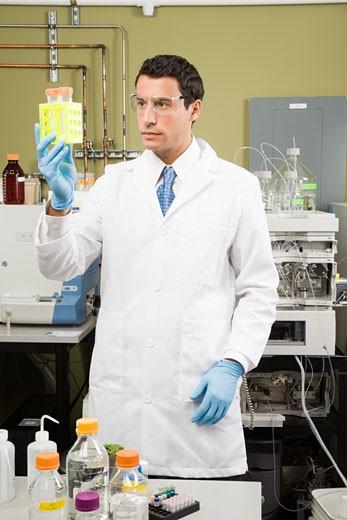 Male scientist examining vials : Stock Photo