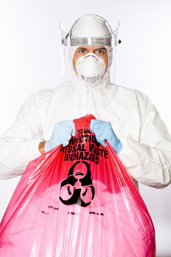 Man in clean suit holding biohazard bag : Stock Photo