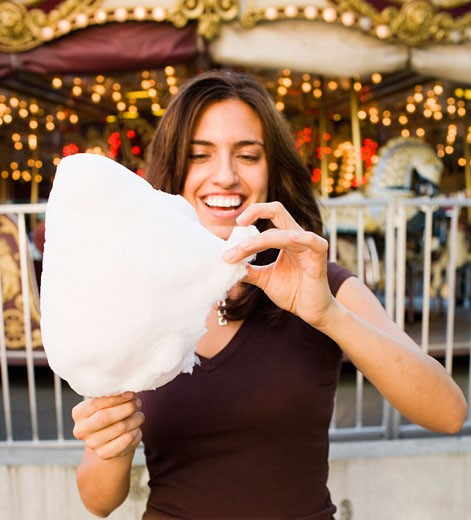Woman eating cotton candy : Stock Photo