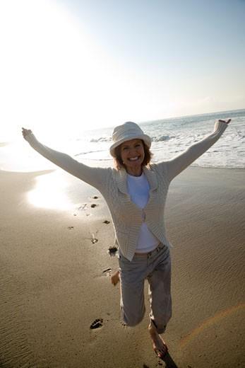Senior woman running on the beach : Stock Photo