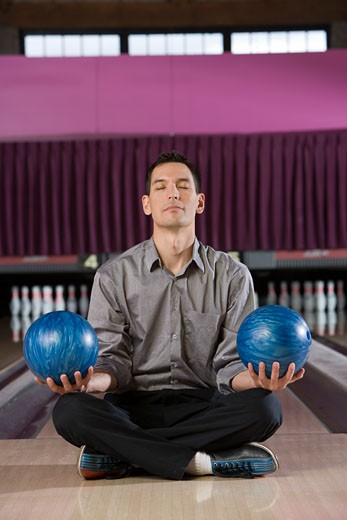 Man meditating with bowling balls in each hand : Stock Photo