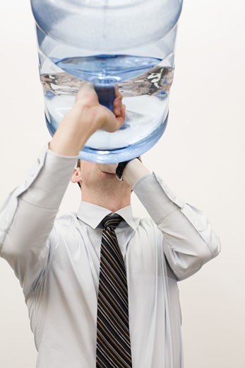 Businessman drinking from water cooler bottle : Stock Photo