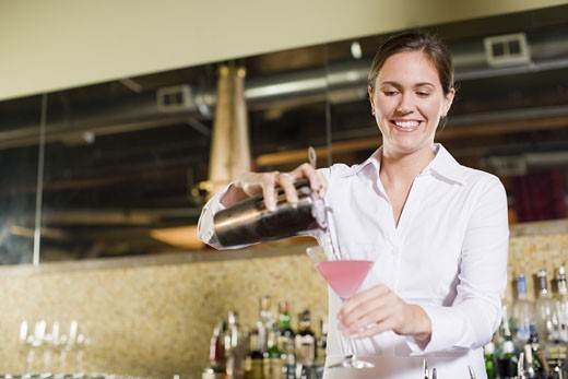 Female bartender pouring cocktail : Stock Photo