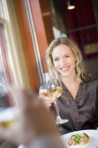 Woman toasting with wine : Stock Photo