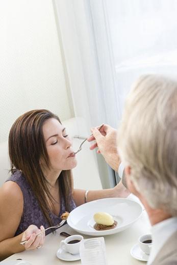 Man feeding woman at restaurant : Stock Photo