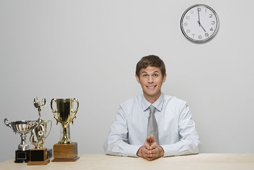 Businessman with trophies on desk : Stock Photo