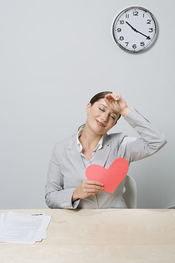 Stock Photo: 1779R-24552 Businesswoman holding cut-out heart