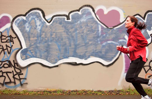 Woman running with graffiti in background  : Stock Photo