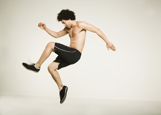 Bare-chested African man jumping : Stock Photo