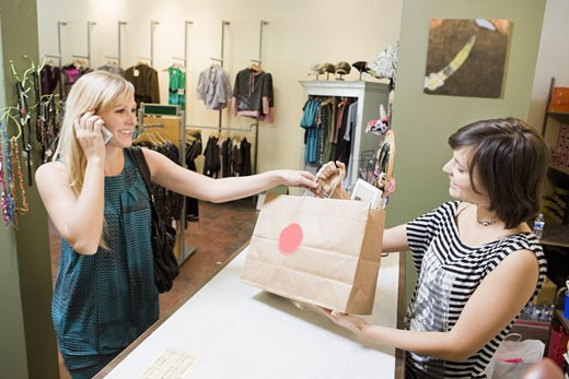 Stock Photo: 1779R-24942 Woman making purchase at boutique