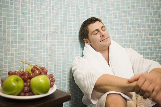 Man in bathrobe leaning on tile wall : Stock Photo