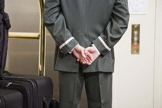 Stock Photo: 1779R-25100 Bellhop with hands behind back
