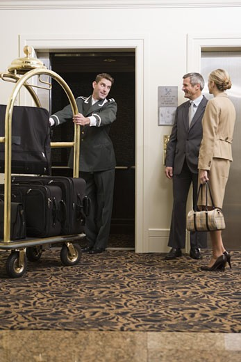 Stock Photo: 1779R-25101 Bellhop pulling luggage cart onto elevator