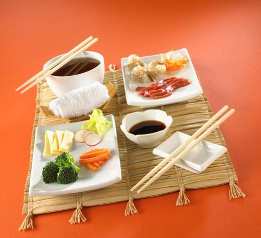 Asian food on mat with chopsticks : Stock Photo