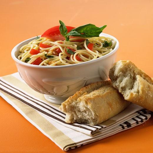 Bowl of pasta next to bread : Stock Photo