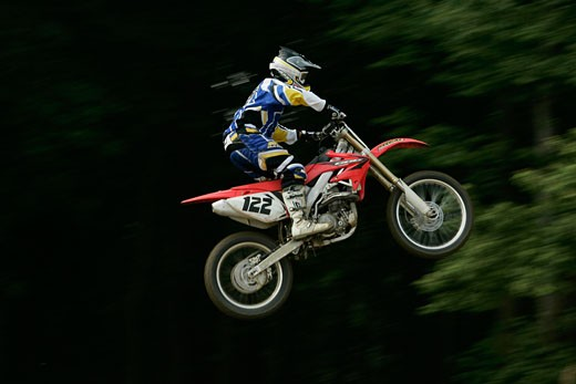 Motorcyclist jumping in mid-air : Stock Photo
