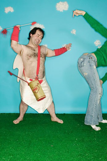 Stock Photo: 1779R-3419 Man in Cupid costume throwing arrow at woman's buttocks