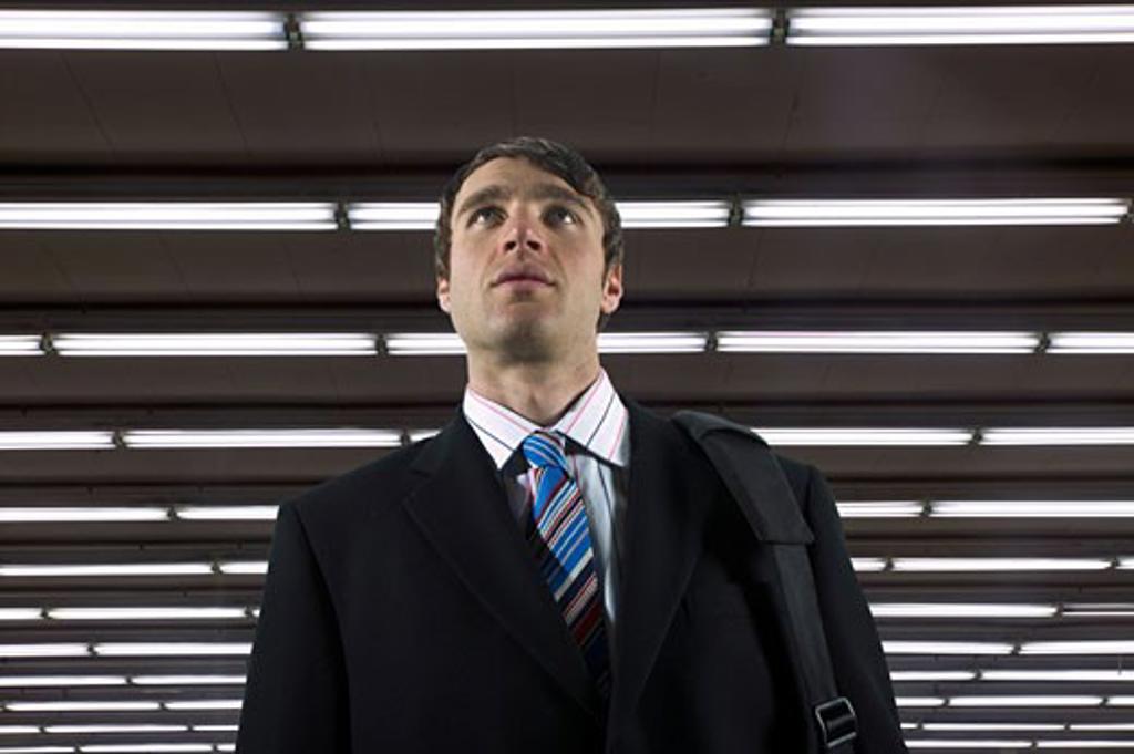 Businessman walking beneath florescent lights : Stock Photo