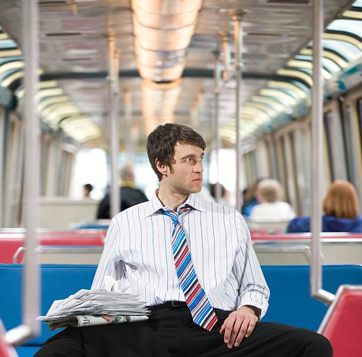 Stock Photo: 1779R-3609 Businessman with newspapers on a train