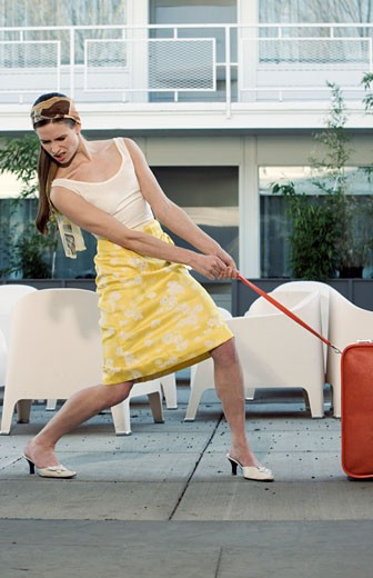 Woman pulling heavy suitcase : Stock Photo