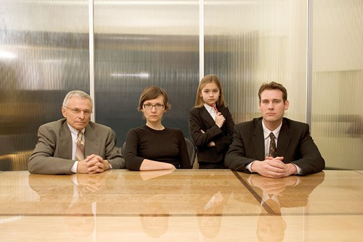 Businesspeople and young girl at conference table : Stock Photo