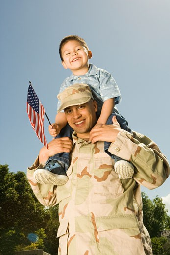 Stock Photo: 1779R-3938 Hispanic military soldier holding son on shoulders