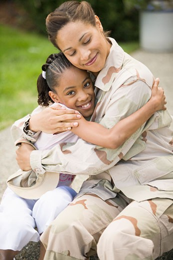 Stock Photo: 1779R-4003 African military soldier hugging her daughter