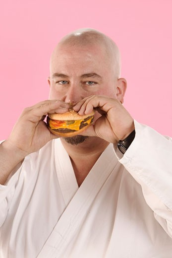 Man in karate outfit eating hamburger : Stock Photo