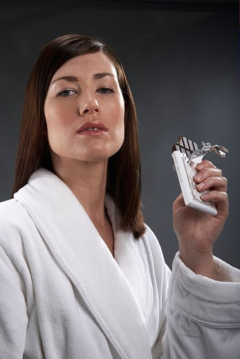 Young woman eating bar of chocolate : Stock Photo
