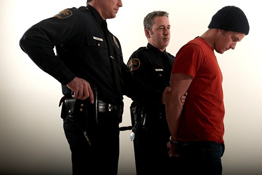 Stock Photo: 1779R-4241 Male police officers arresting a young man