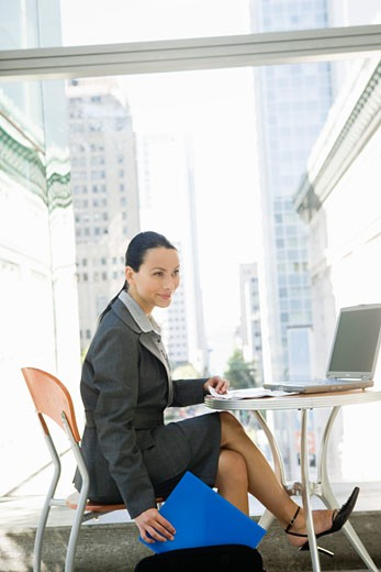 Businesswoman sitting at table : Stock Photo