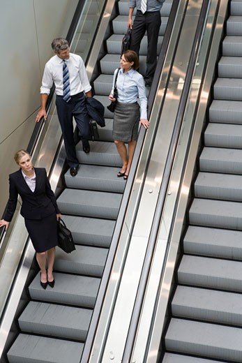 Stock Photo: 1779R-4664 Businesspeople standing on escalator