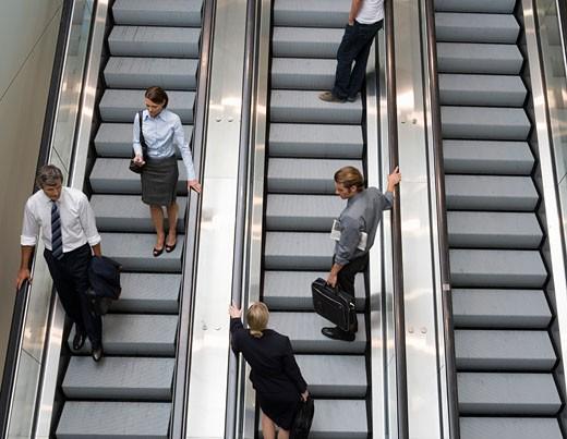 Businesspeople standing on escalators : Stock Photo