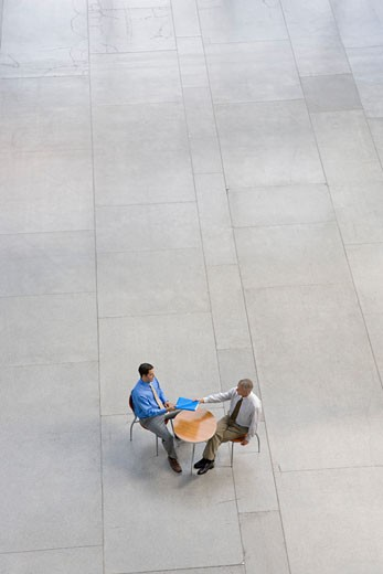 Businessmen exchanging paperwork : Stock Photo