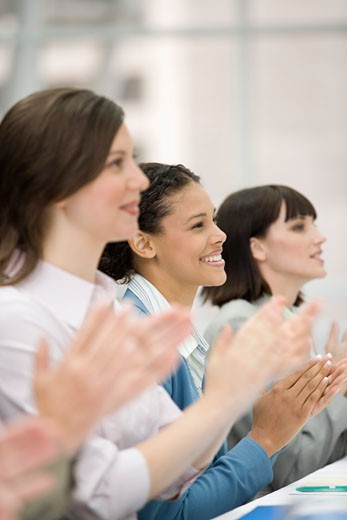 Businesswomen clapping at meeting : Stock Photo
