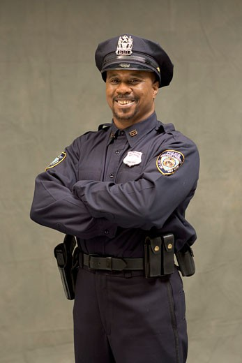 Stock Photo: 1779R-5117 African policeman standing with arms crossed
