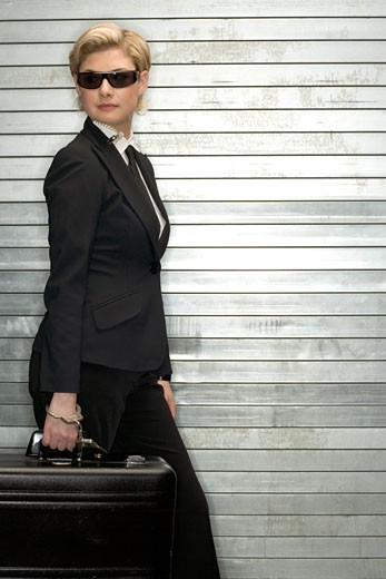 Sneaky businesswoman carrying briefcase : Stock Photo