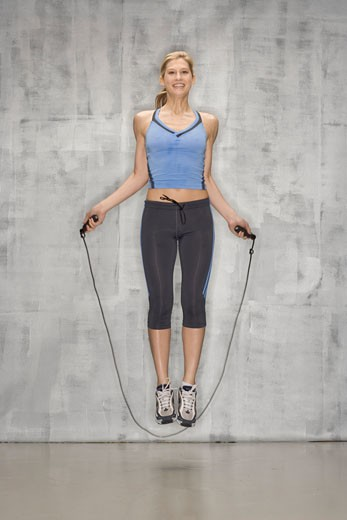 Female athlete jumping rope in mid-air : Stock Photo