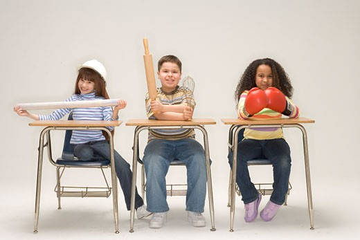 Children with occupational objects at school desks : Stock Photo