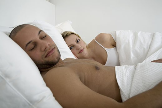 Stock Photo: 1779R-5780 Young woman looking at sleeping young man in bed