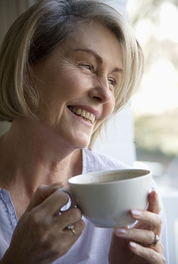 Stock Photo: 1779R-5876 Senior woman drinking a cup of coffee by window