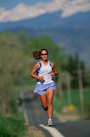 Stock Photo: 1779R-6393 Woman jogging on paved road