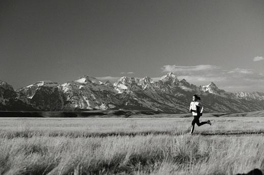 Woman jogging through meadow : Stock Photo
