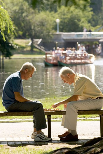 Senior men playing checkers on park bench : Stock Photo