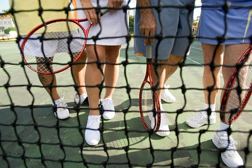Stock Photo: 1779R-6948 Low section view of people holding rackets on tennis court