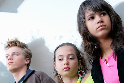 Bored teenagers standing next to wall : Stock Photo